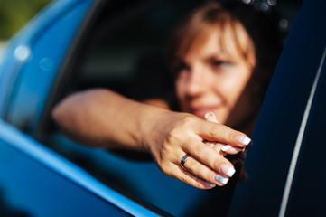 close-up portrait of pretty shy bride in a car window