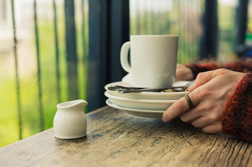 Woman with empty plates and mug