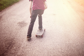 Boy cruising on a longboard at sunset