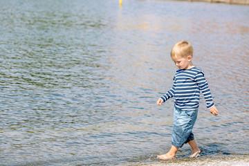 Little preschool boy walking on beach outdoors