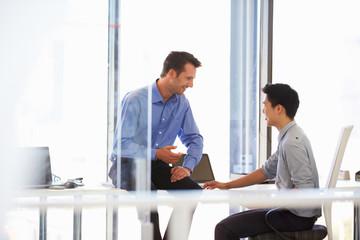 Two men talking in a modern office