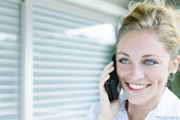 Happy young blonde beautiful woman on the phone