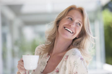 Happy mature woman smiling with a cup of tea
