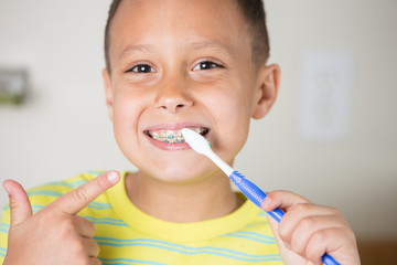 Boy brushing his teeth and pointing.