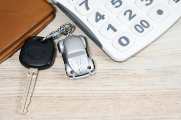 Car key with calculator and wallet on wood table
