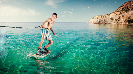 Wakeboarder rides a board on sea in. Wakeboarding on beach. Wall mural