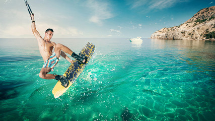 Wakeboarder making tricks on sea. Wakeboarding on beach.
