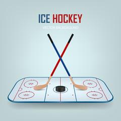 Ice hockey puck and crossed sticks on field.