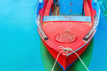 Empty red wooden boat with blue broadside moored in port with s