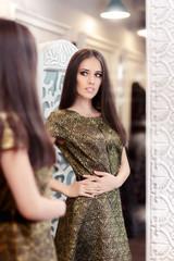 Beautiful Girl in Golden Brocade Dress Looking in the Mirror
