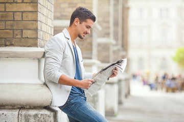 Young man reading newspaper on the city street