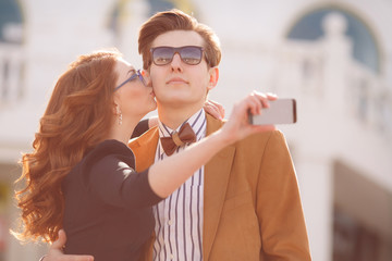 A loving couple is photographed on a smartphone in town