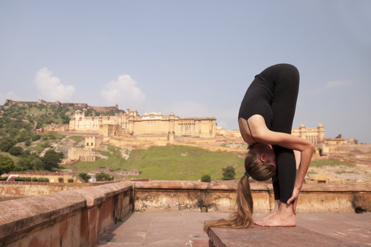 Young female practising yoga pose Standing forward fold