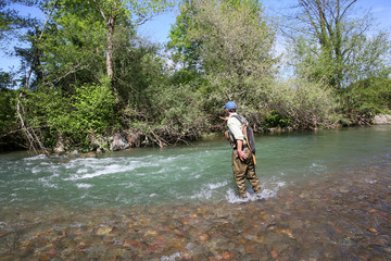 Fisherman in river catching brown trout