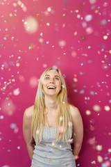 lachende junge frau steht im konfetti-regen