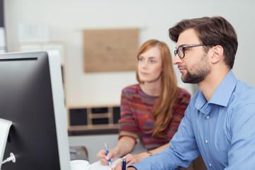zwei kollegen arbeiten zusammen am computer