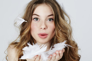 Teenage girl blowing feathers