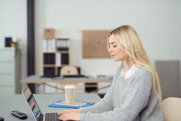 junge frau schreibt am laptop