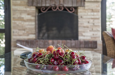 apricots and cherry fruit in glass plate on table in living room