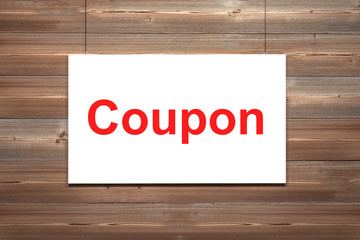 white canvas on wooden wall torn to reveal coupon
