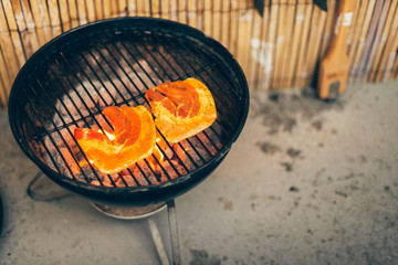 Wedges of fresh pumpkin grilling on a BBQ