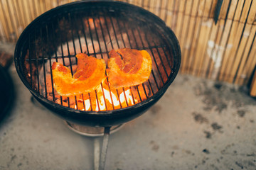 Fresh pumpkin grilling over hot coals on a BBQ