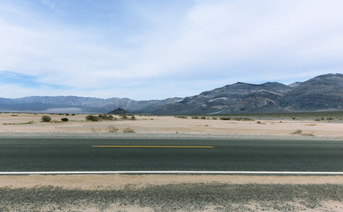Road in Mojave desert with cloudy sky and striped mountains
