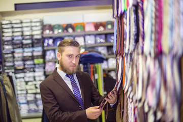 young man chooses a tie, costume shop