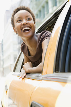 African woman looking out taxi window in wonder