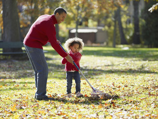 African father and daughter raking leaves