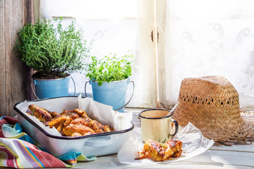 Hot chicken wings with herbs and sauce in rustic kitchen
