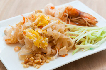 Seafood pad Thai dish of stir fried rice noodles on a square white dish