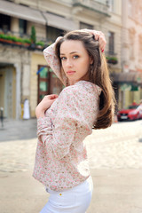 Beautiful brunette woman walking on street at sunny day