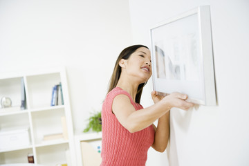 Asian woman hanging picture on wall