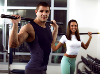 beautiful woman in gym with personal trainer