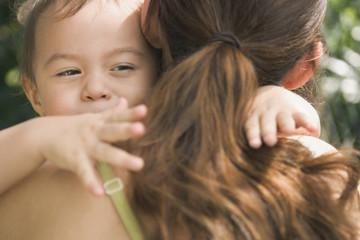 Hispanic baby hugging mother