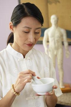 Asian woman using mortar and pestle