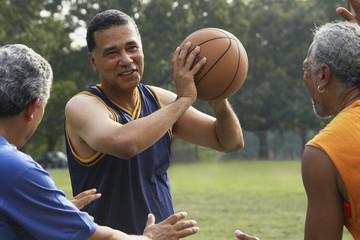Multi-ethnic men playing basketball