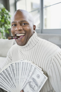 African man smoking cigar and holding 100 dollar bills