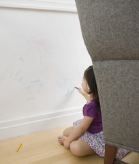 Toddler girl drawing on wall with crayons