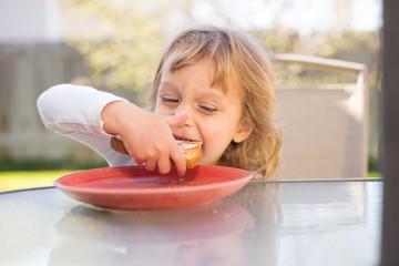 Little girl eating outside.
