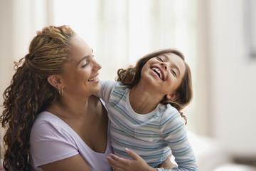Hispanic mother hugging laughing daughter