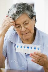 Senior Hispanic woman looking at pill organizer