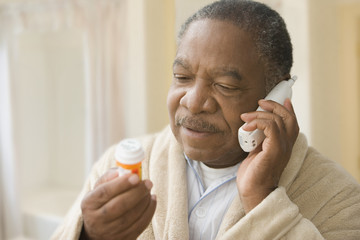 African man holding prescription bottle and talking on phone