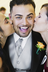 Groom being kissing by two women