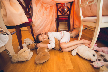 cute girl sleeping on floor with toys at bedroom