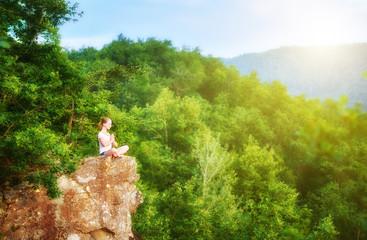 Fototapete - woman meditating in lotus posture, doing yoga on top of the moun