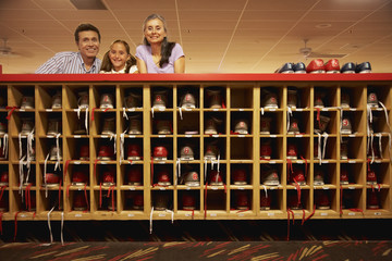 Hispanic family leaning on counter at bowling alley