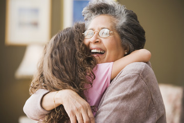Hispanic grandmother hugging granddaughter