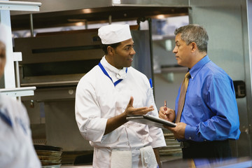 Hispanic businessman talking to chef